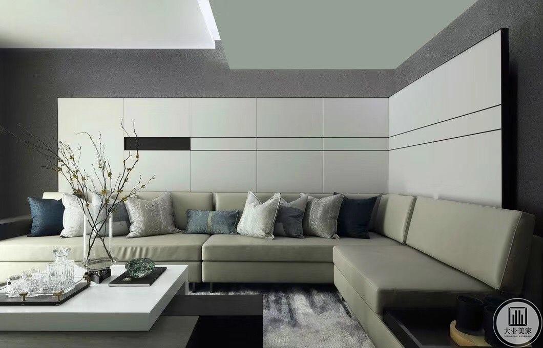 """设计师选用灰色调纯色沙发,抱枕配色搭配巧妙,L形的白色背景墙刚好搭配沙发,桌上的花艺作品搭配精致巧妙,表现了女主人极致的""""雅""""和设计师优秀的诠释能力。"""