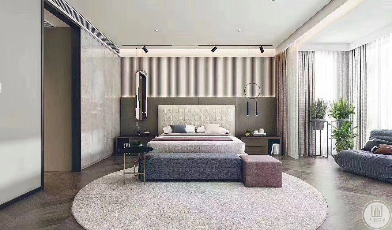 本案卧室空间较大,搭配简约,设计师采用木质地板搭配圆形地毯,质地上乘的布艺,背景墙和灯具别致独特,绿植与柔软的沙发给人一种放松舒适的感觉。