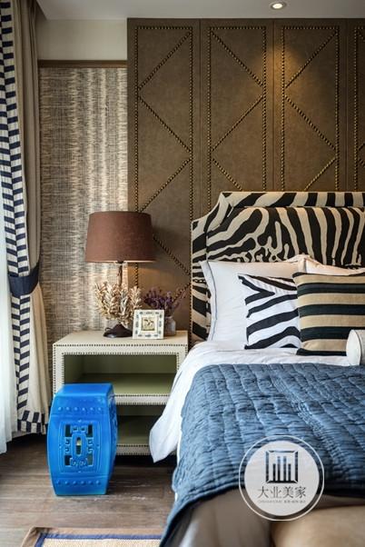 为了能展现美式风格的典雅,卧室墙面上做了棕色的软包造型,并且在床头柜的位置安装台灯,夜晚的时候更是营造了温馨淡雅气氛。