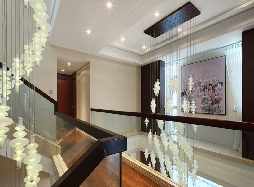 楼梯处直接以水晶吊灯下垂至餐厅处,吊灯增加室内现代感,实木楼梯与吊灯是古典与现代的结合,将新中式情怀包含其中。